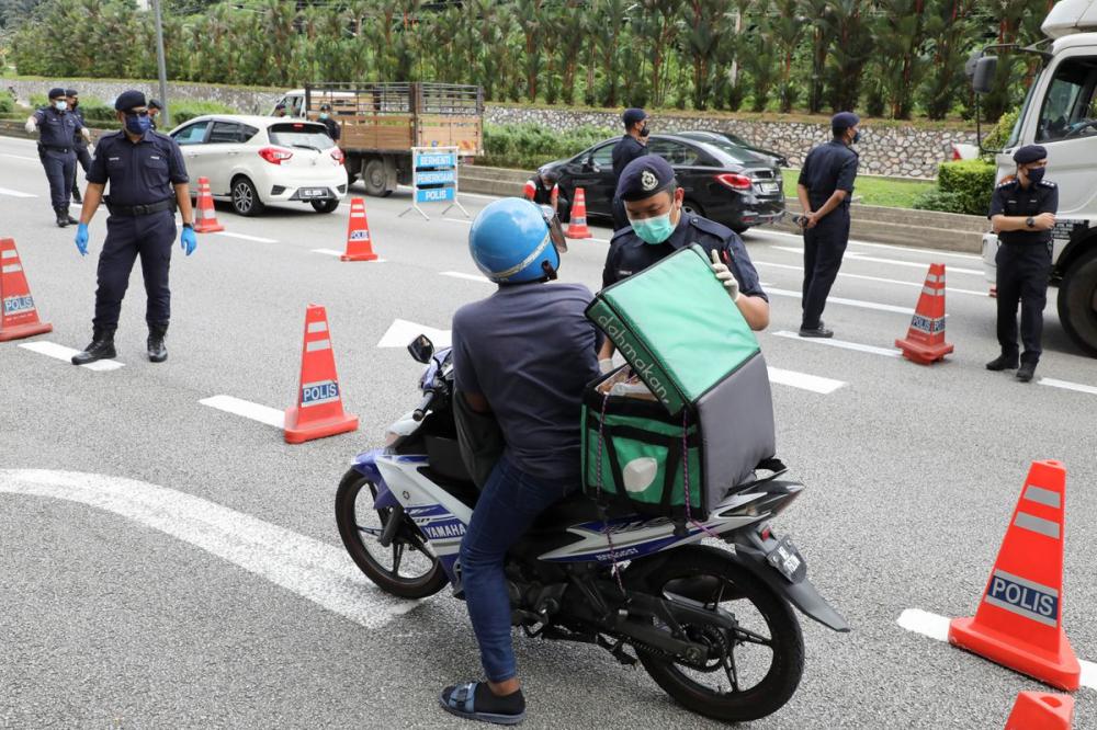 Nhân viên cảnh sát kiểm tra các phương tiện giao thông tại một chốt chặn trong bối cảnh bùng phát dịch bệnh COVID-19 ở Kuala Lumpur, Malaysia