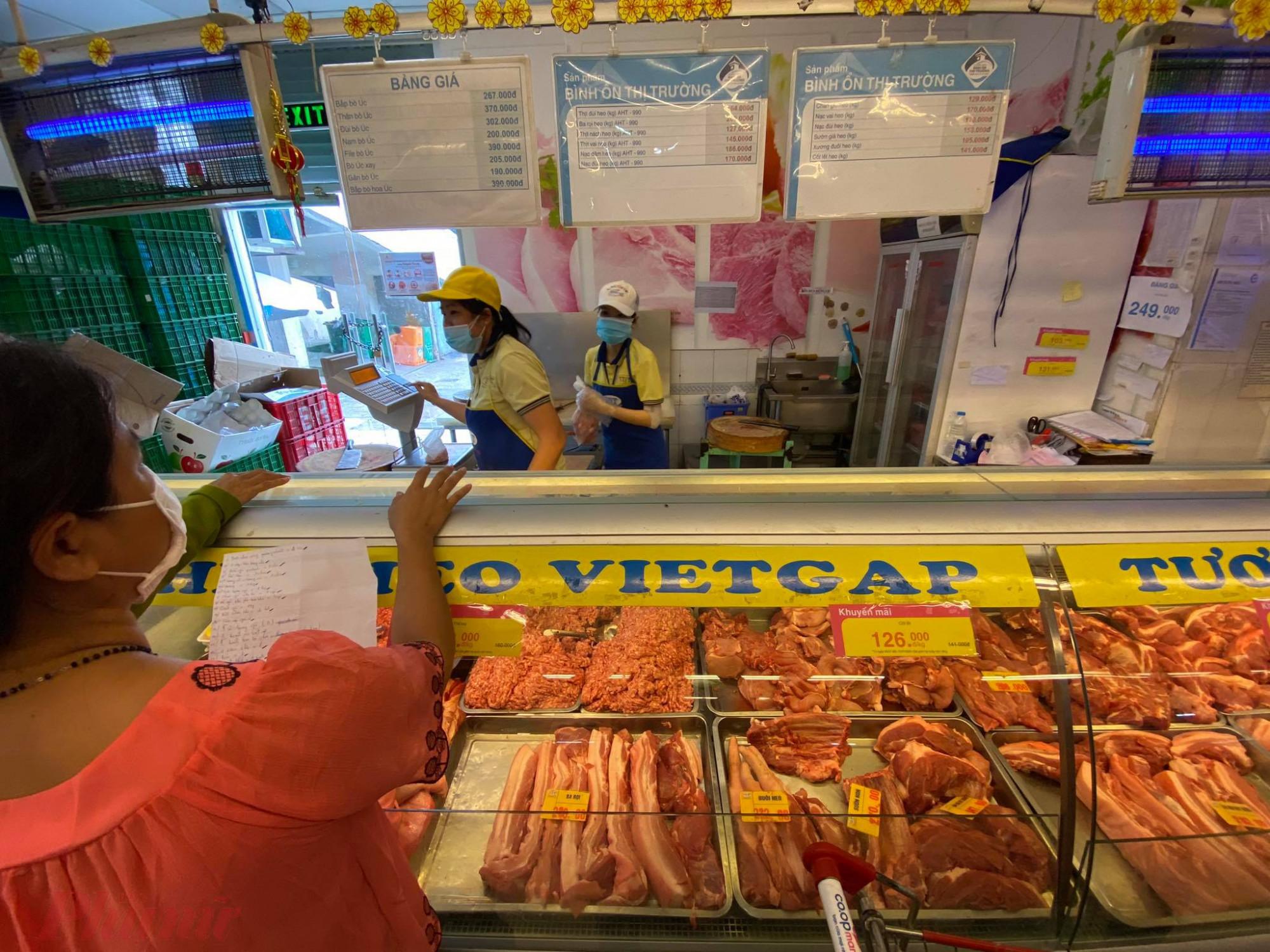 Một khách hàng đang chuẩn bị nhận thịt theo danh sách đã soạn hân viên đang soạn thực phẩm cho khách