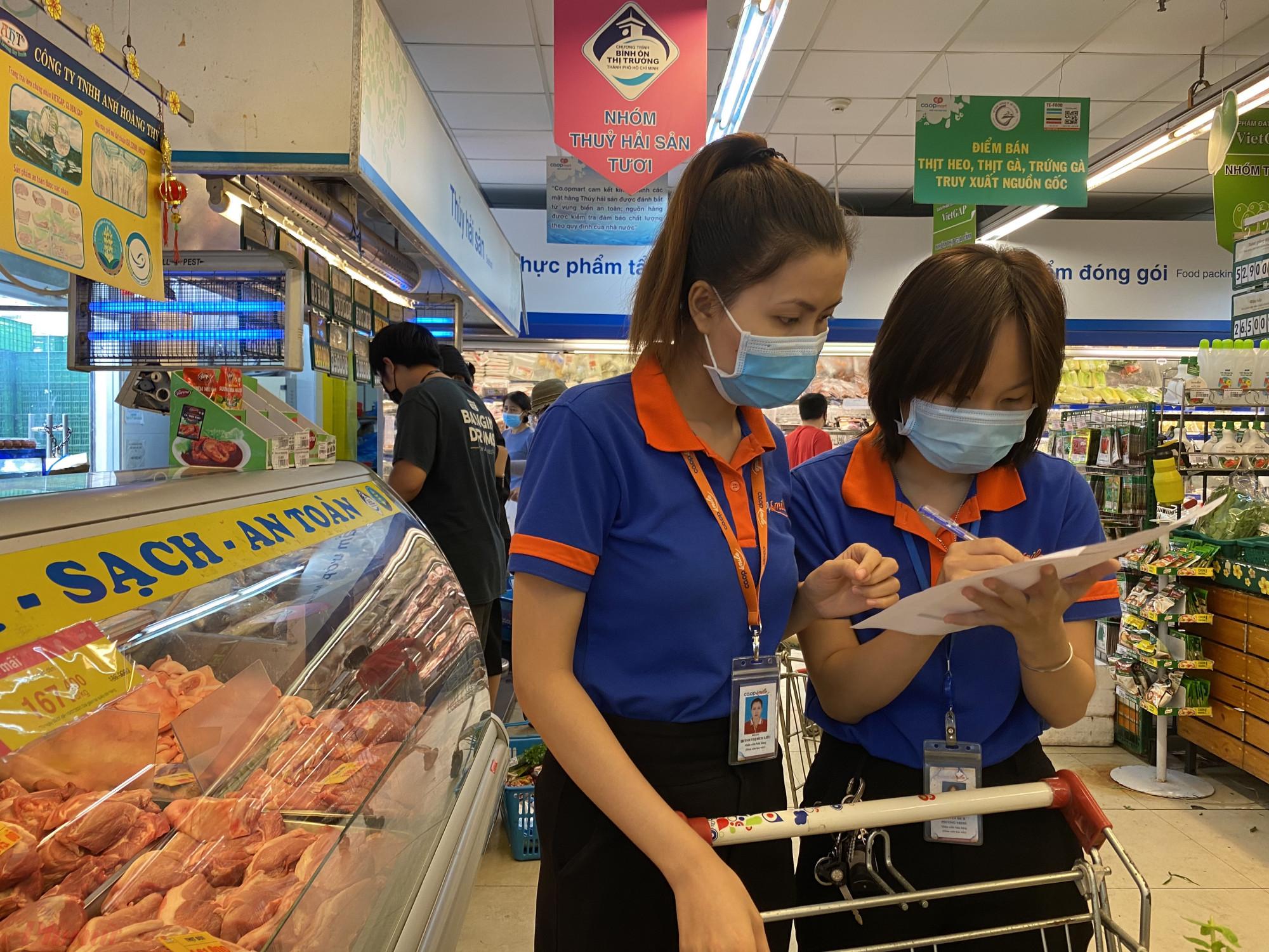 Nhân  viên siêu thị đang đi  chợ  thay cho  khách  hàng  tại  siêu  thị Co.op  Nhiêu  Lọc  trong sáng đầu tiên  thực  hiện giãn các xã hội tại TPHCM. Ảnh: Quốc  Thái
