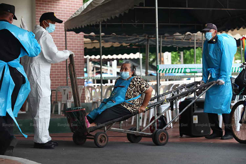 Nhân viên y tế dùng xe đẩy tay để di chuyển một phụ nữ lớn tuổi đến địa điểm xét nghiệm COVID-19 nằm trong chợ đồ tươi Mahanak ở Bangkok