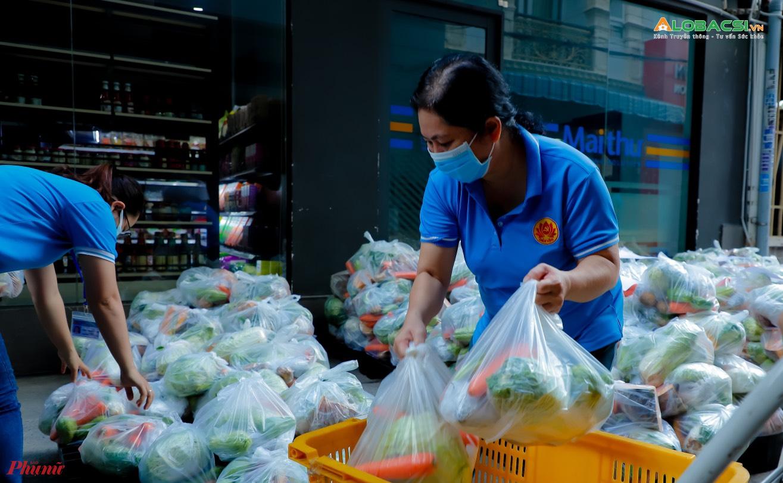 Các lực lượng phân loại rau củ thành từng túi quà để tặng các gia đình