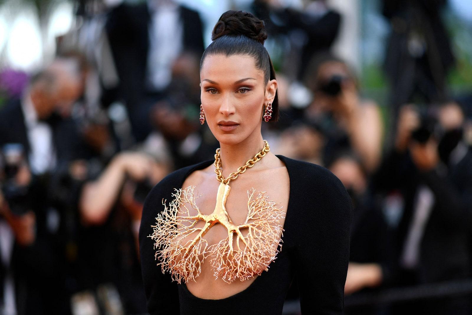 Ở ngày thứ 6 của LHP Cannes 2021, siêu mẫu Bella Hadid khiến thảm đỏ nóng hơn khi diện thiết kế khoe trọn vòng 1. Cô mang một chiếc dây chuyền hình 2 lá phổi bằng vàng và dùng chính món trang sức cỡ lớn này che cho phần ngực.