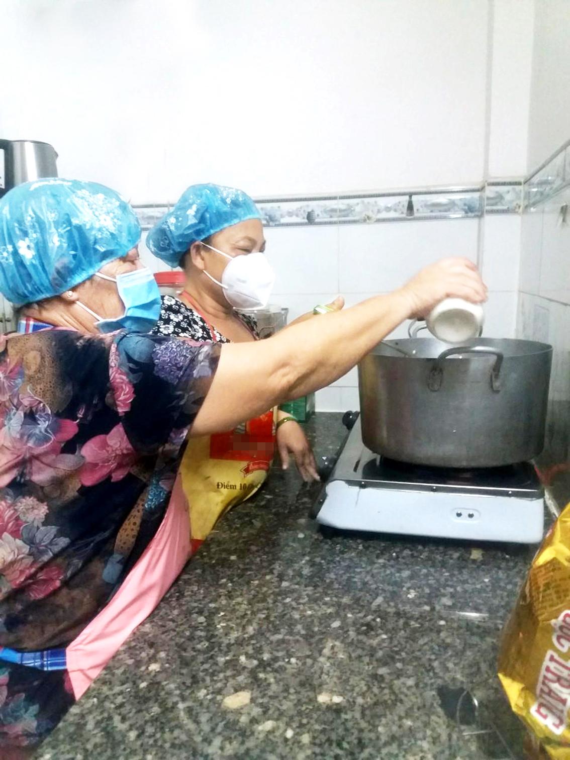 Mẹ con cô Cúc - chị Hằng nấu cơm cho khu cách ly y tế - Ảnh: S.A.