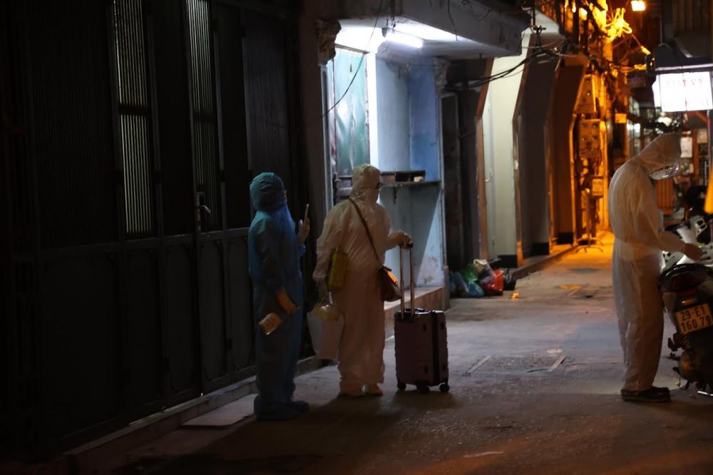 Bệnh nhân F0 mang đồ đạc ra khỏi nhà, chuẩn bị lên xe cứu thương