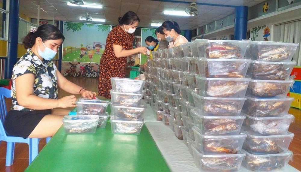Các cô giáo Trường mầm non Hoa Mai (H.Phú Vang, tỉnh Thừa Thiên - Huế) chế biến món cá kho rim gửi tặng bà con TP.HCM - ẢNH: THUẬN HÓA