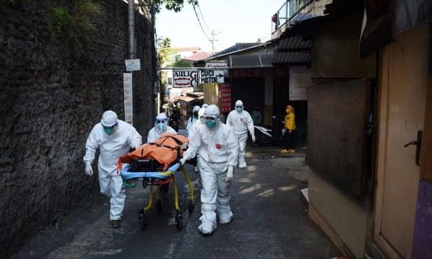 Các nhân viên y tế khiêng thi thể một người chết bằng Covid-19 khi đang cách ly tại nhà ở Bandung, Indonesia. Ảnh: Timur Matahari / AFP / Getty Images