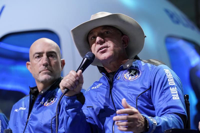 Mark Bezos (trái), lắng nghe anh trai Jeff Bezos, người sáng lập Amazon và công ty du lịch vũ trụ Blue Origin, mô tả trải nghiệm chuyến bay sau khi họ được phóng lên từ sân bay vũ trụ gần Van Horn, Texas, ngày 20/7 - Ảnh: AP