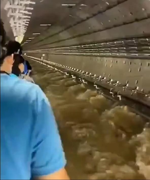 Các hành khách được giải cứu di chuyển bên cạnh dòng nước chảy siết trong đường ngầm