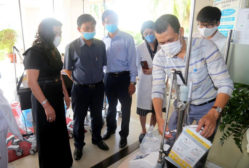 Bà Đặng Thị Kim Oanh cùng đại diện Ủy ban Mặt trận Tổ quốc Việt Nam tỉnh Bình Dương, đại diện lãnh đạo Bệnh viện Đa khoa tỉnh Bình Dương (thứ tự từ trái qua) theo dõi cách thức vận hành hệ thống máy oxy - Ảnh: Địa ốc Kim Oanh