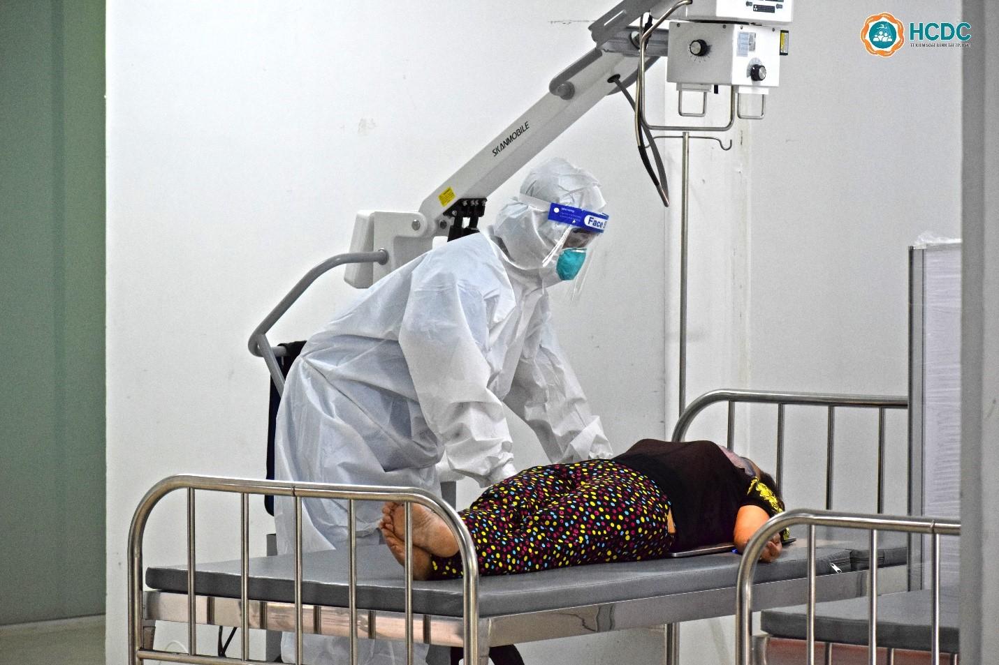 Nhân viên y tế hướng dẫn bệnh nhân tư thế nằm để chụp X-Quang. Ảnh: HCDC
