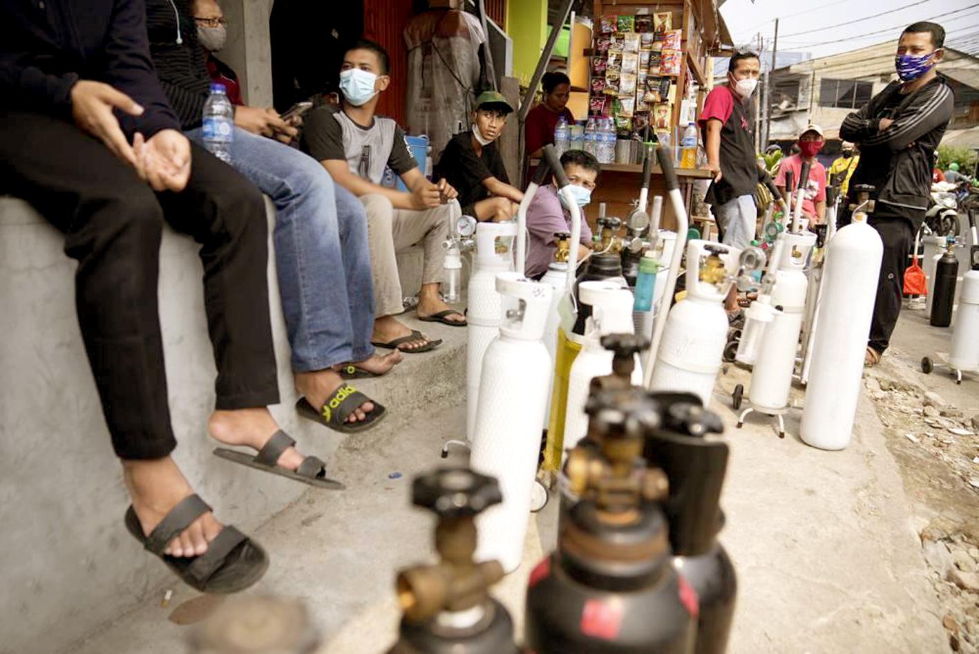 Người dân xếp hàng chờ nạp đầy bình ô-xy cho thân nhân mắc COVID-19 tại một trạm nạp ở Jakarta, Indonesia - ẢNH: AP