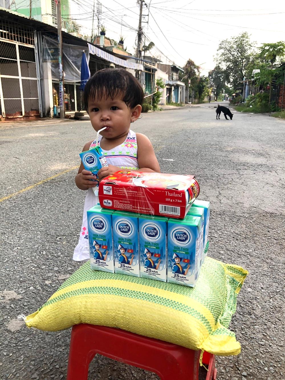 Trẻ nhỏ tại khu bến đò Bình Mỹ (ấp 1, xã Bình Mỹ, huyện Củ Chi, TPHCM) phần lớn là dân tộc Khơ-me cóhoàn cảnh rất khó khăn, thiếu thốn. Nhận được sữa, nhiều bé khui ra uống tại chỗ vì đã lâu rồi chưa được uống - Ảnh: CGHL