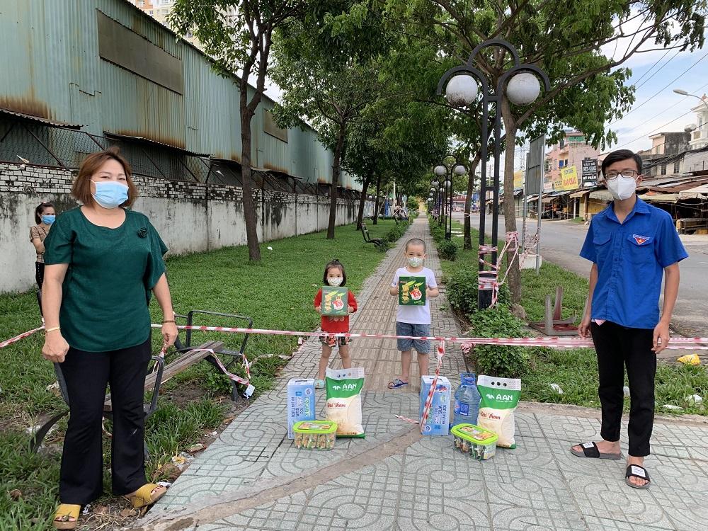 Đại diện Mặt trận Tổ quốc Việt Nam TPHCM trao tặng sữa Cô Gái Hà Lan cho các bé tại các khu vực bị phong toả do có ca nhiễm trên địa bàn quận 12, quận 7 và nhiều quận huyện khác - Ảnh: CGHL