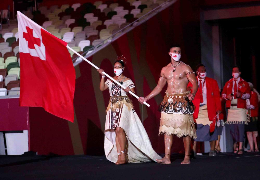 Pita Taufatofua (phải) cầm cờ cùng với Malia Paseka khi họ dẫn đầu đoàn thể thao Tonga trong Lễ khai mạc