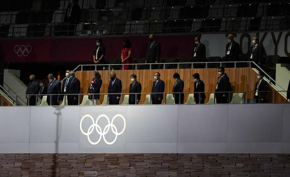 Nhật hoàng Naruhito, chủ tịch IOC Thomas Bach và các đại biểu khác đứng yên chào cờ trong lễ khai mạc