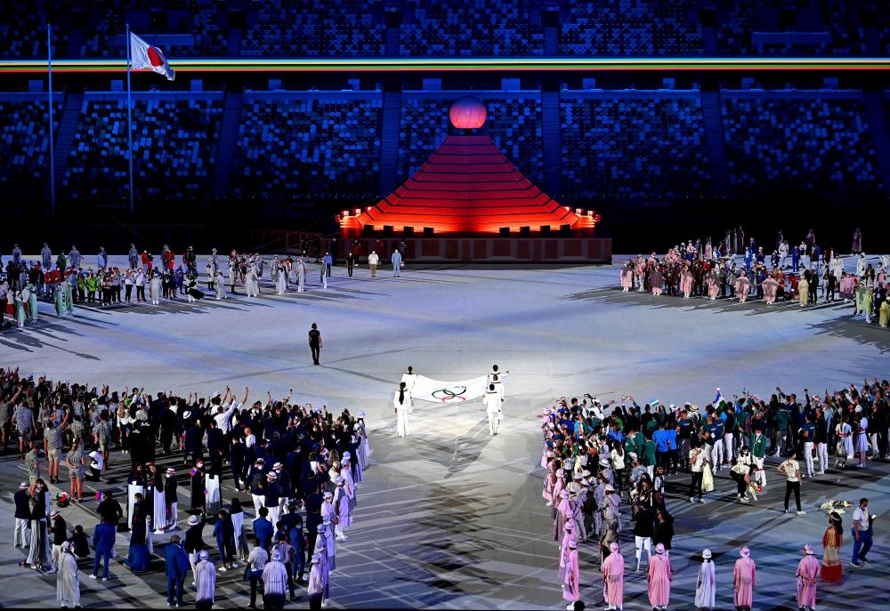 Cờ Olympic được mang vào sân vận động bởi sáu vận động viên, những người đã cống hiến thời gian và tài năng để phục vụ như những chiến sĩ tuyến đầu chống đại dịch trong cộng đồng địa phương của họ.