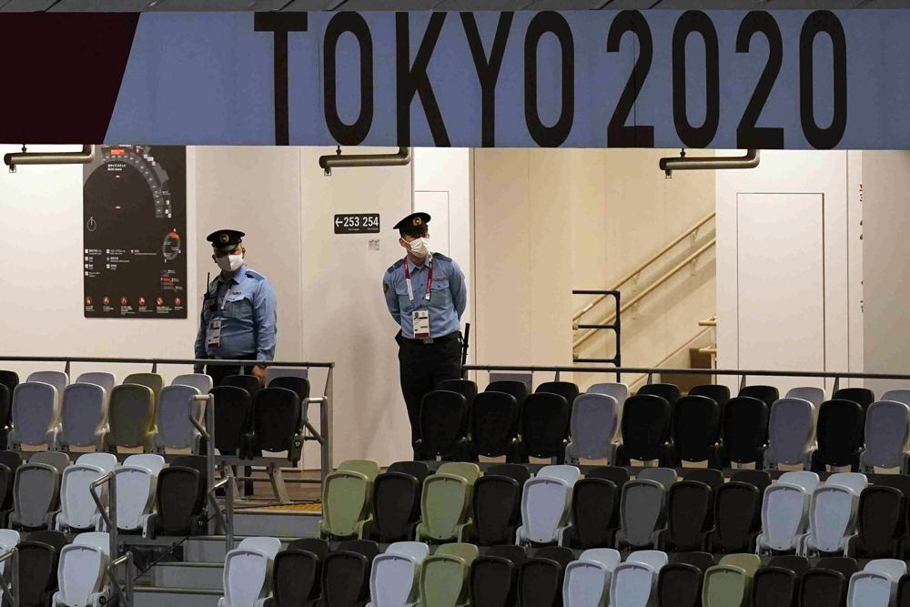 Nhân viên an ninh theo dõi lễ khai mạc trong một sân vận động Olympic trống rỗng