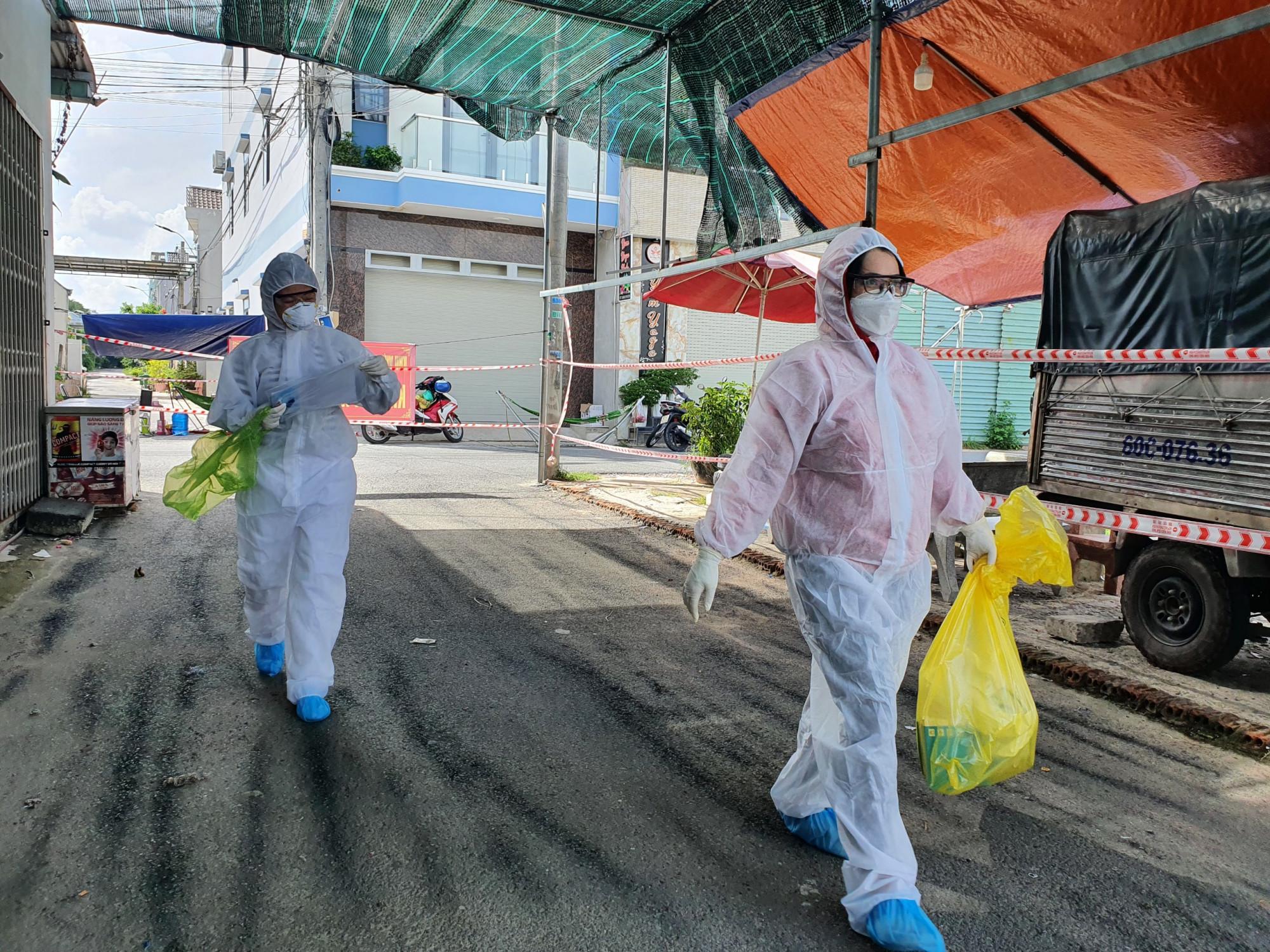Nhân viên y tế trên đường đi lấy mẫu xét nghiệm cho công nhân ở trọ tại xã Thạnh Phú, huyện Vĩnh Cửu - Ảnh: HL