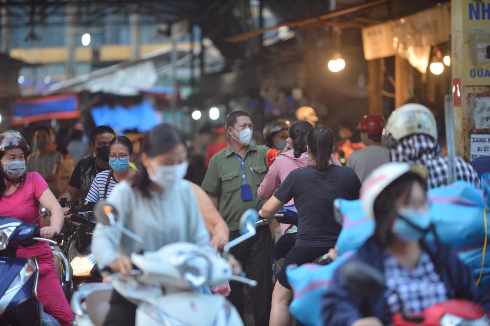 nhân viên bảo vệ kiểm tra thân nhiệt tại cổng ra vào chợ.