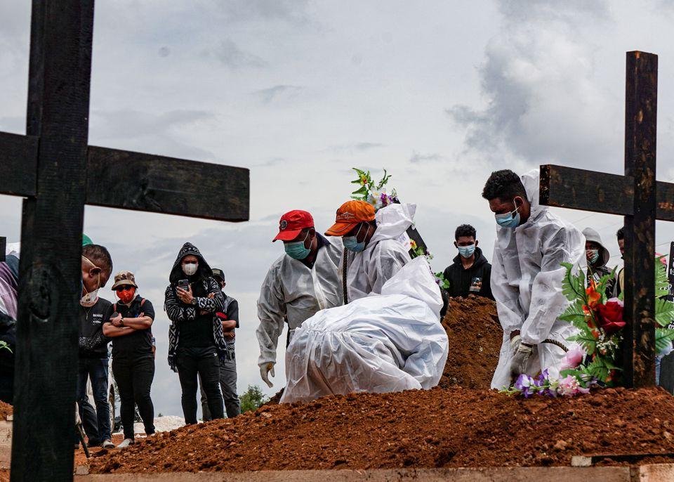 Những người bốc mộ đeo thiết bị bảo hộ cá nhân (PPE) chôn một quan tài tại một khu vực chôn cất do chính phủ cung cấp cho các nạn nhân của COVID-19, khi các ca nhiễm gia tăng ở Jayapura, Papua, Indonesia