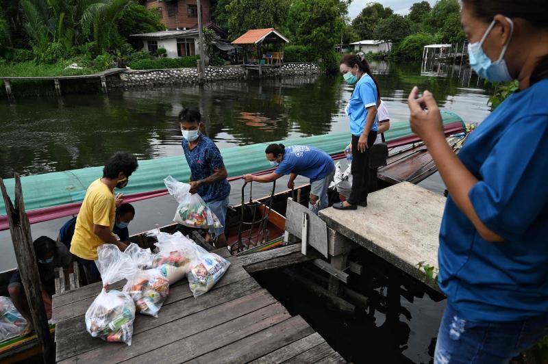 Các tình nguyện viên địa phương từ Tổ chức Trợ giúp Cộng đồng Bangkok bốc dỡ thực phẩm cho các gia đình trong một cộng đồng hẻo lánh ở quận Phra Kanong