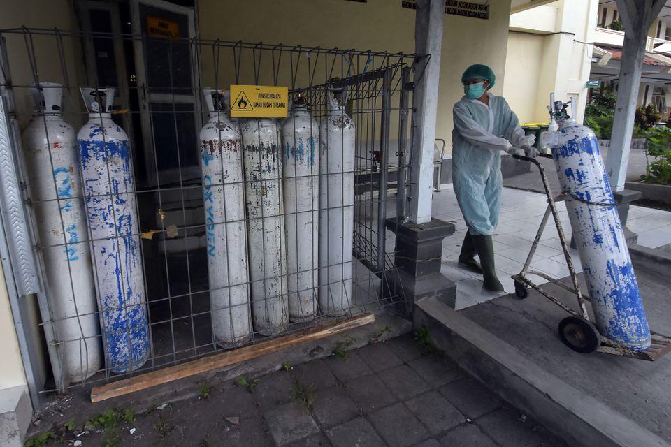 Một nhân viên y tế kéo một bình oxy để được chuyển đến khu cấp cứu tại một bệnh viện do chính phủ điều hành trong bối cảnh dịch bệnh bùng phát ở Denpasar, Bali