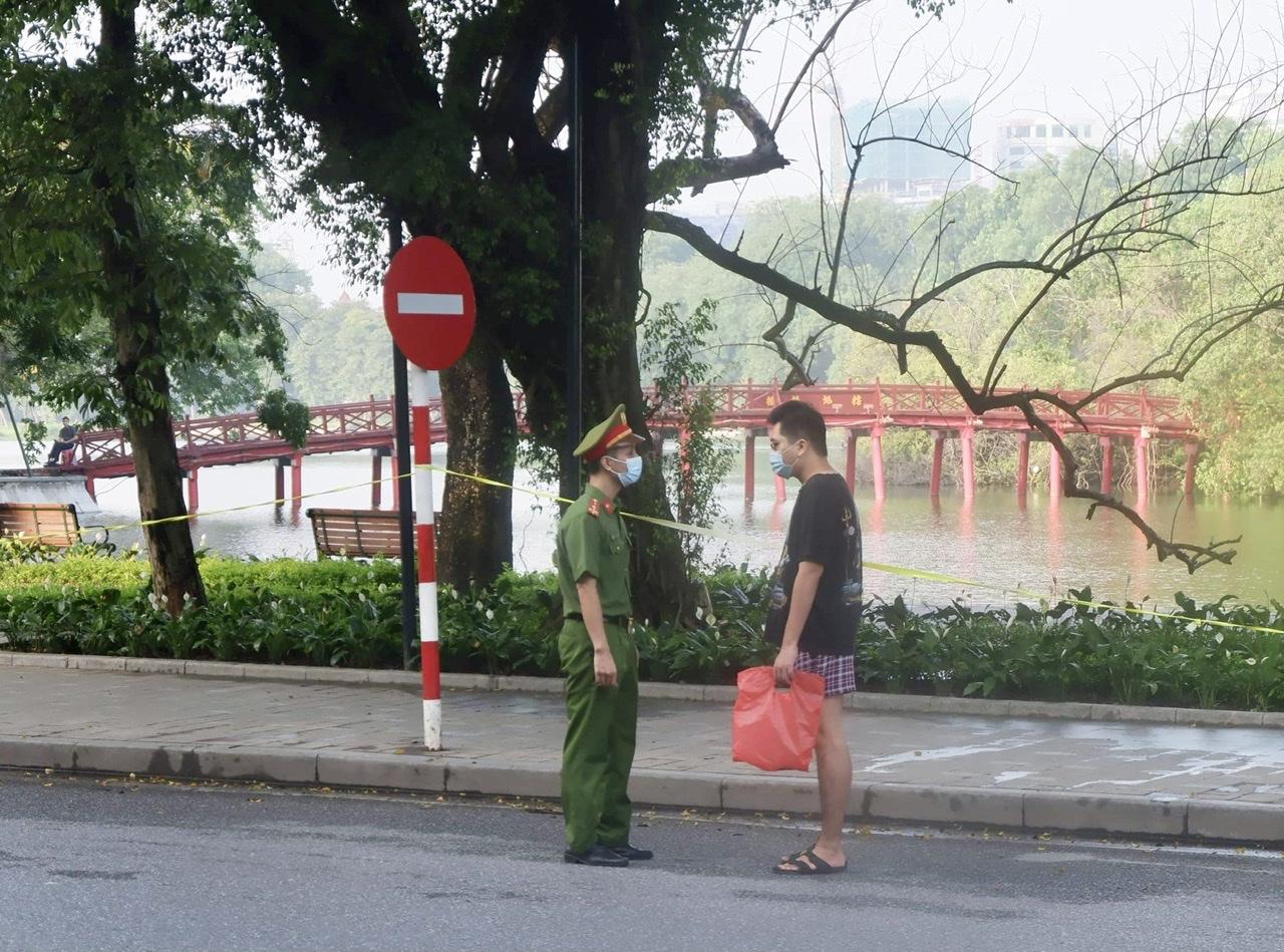 Lực lượng chức năng nhắc nhở người dân đi tập thể dục.