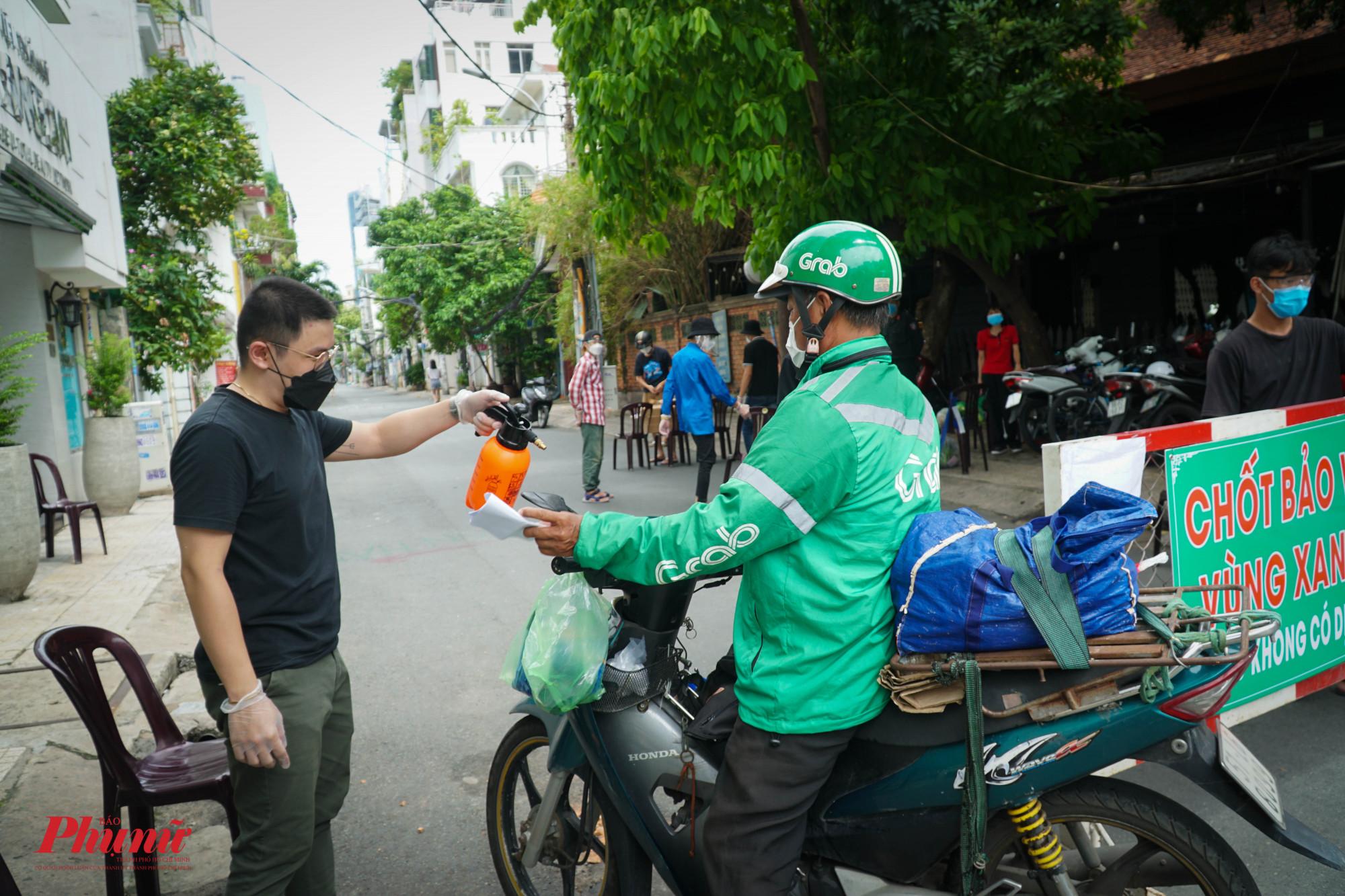 Sau khi sát khuẩn tay và món hàng, người giao hàng mới được vào trong khu phố