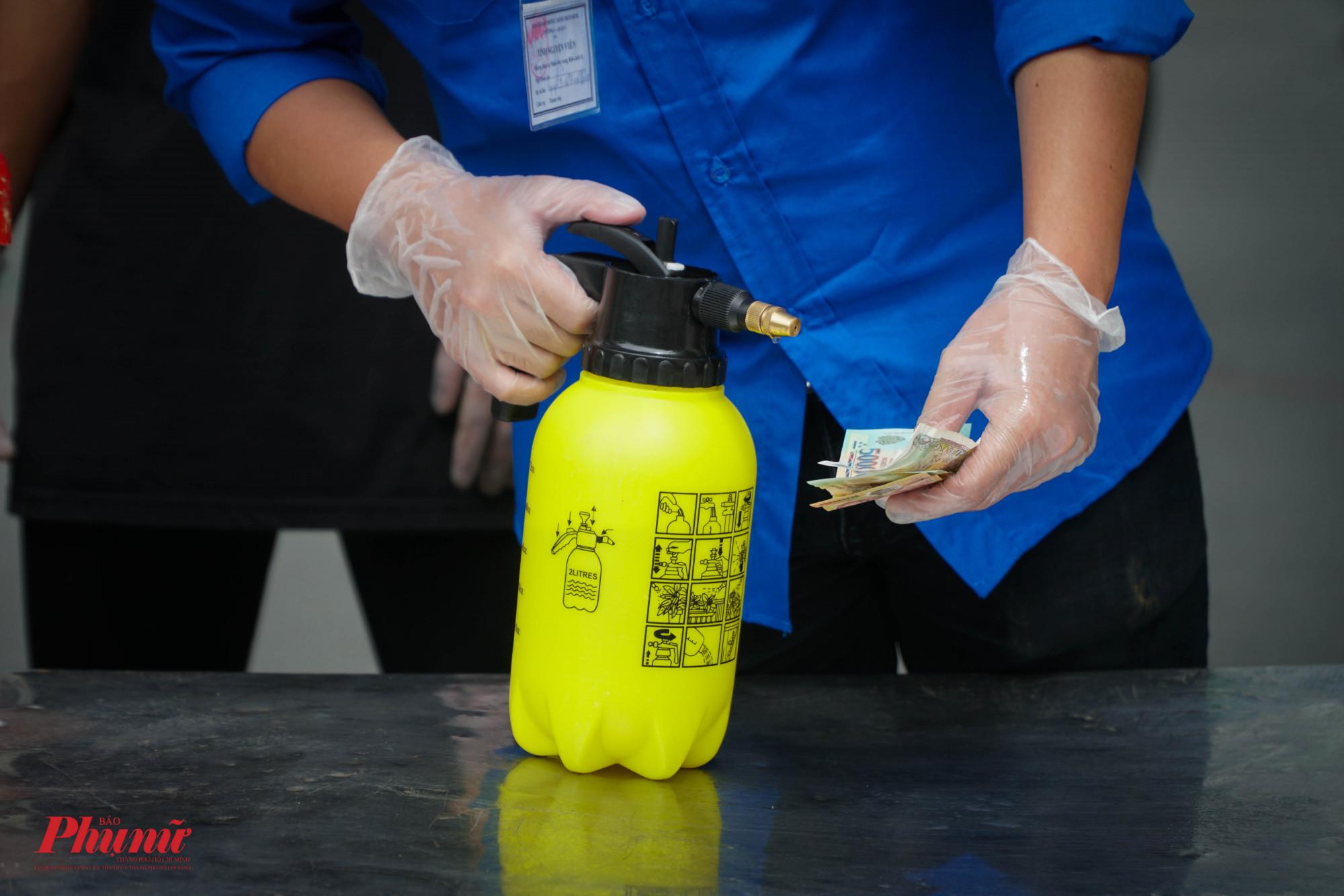 Phàn tiền trả cho món hàng cũng được lực lượng phun khử khuẩn trước khi gửi lại nhân viên giao hàng