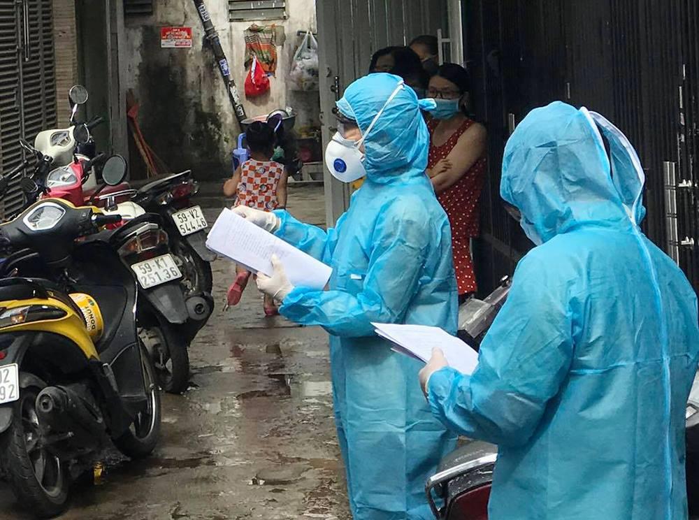 Nhân viên y tế vận động người dân khu vực có ca nghi nhiễm ra lấy mẫu xét nghiệm