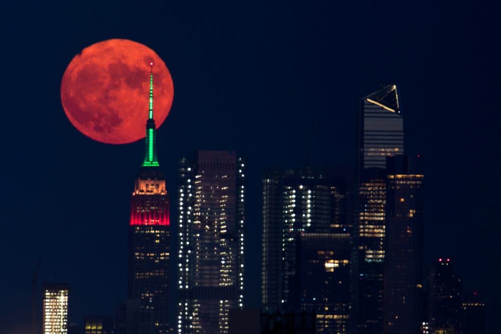 Trăng tròn màu cam mọc lên phía sau Tòa nhà Empire State ở Thành phố New York (Mỹ) đêm 23/7 - Ảnh: Reuters