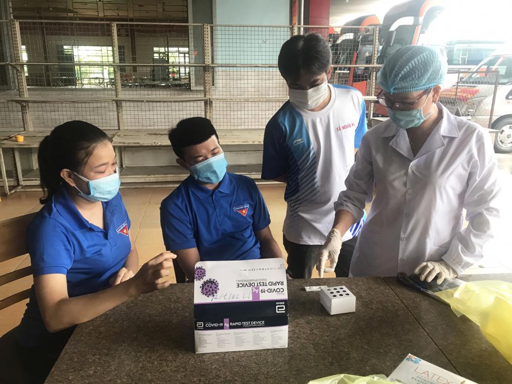 Nhân viên y tế đang hướng dẫn các tình nguyện viên nhận biết kết quả test nhanh SARS-Cov- 2