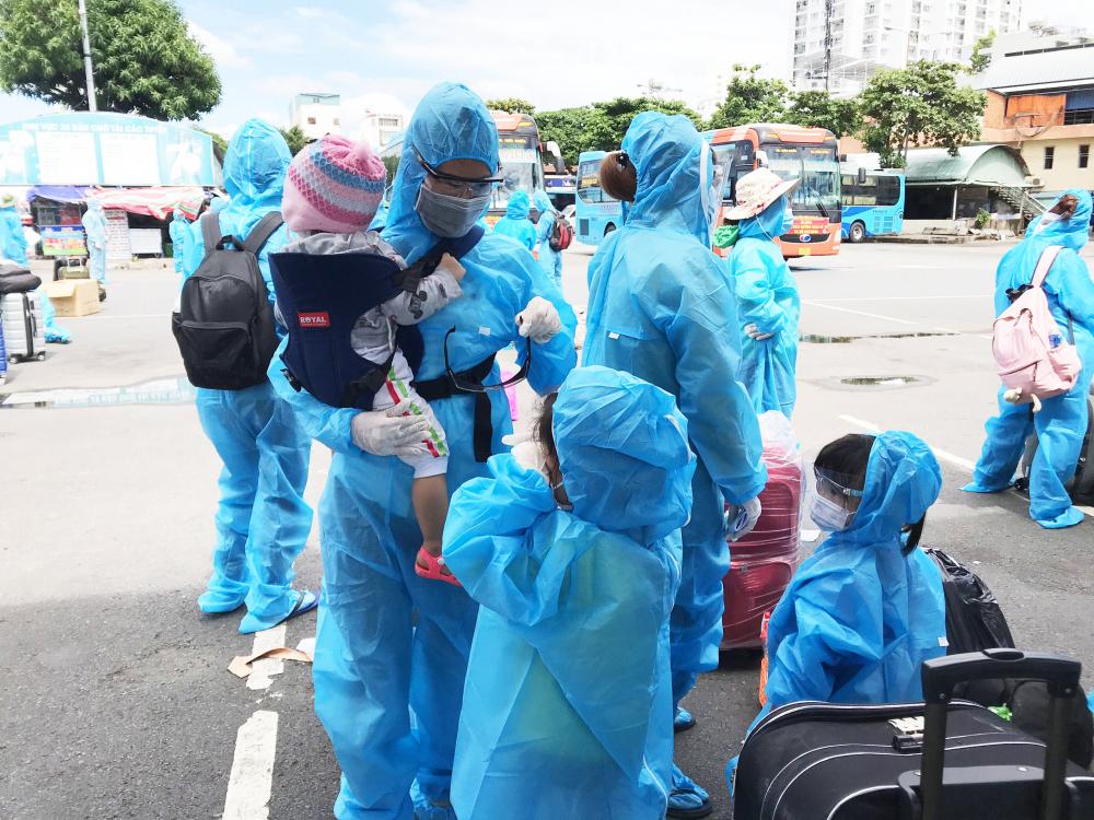 Các em bé bên cha mẹ trong những bộ đồ phòng dịch COVID - 19 trước khi về quê