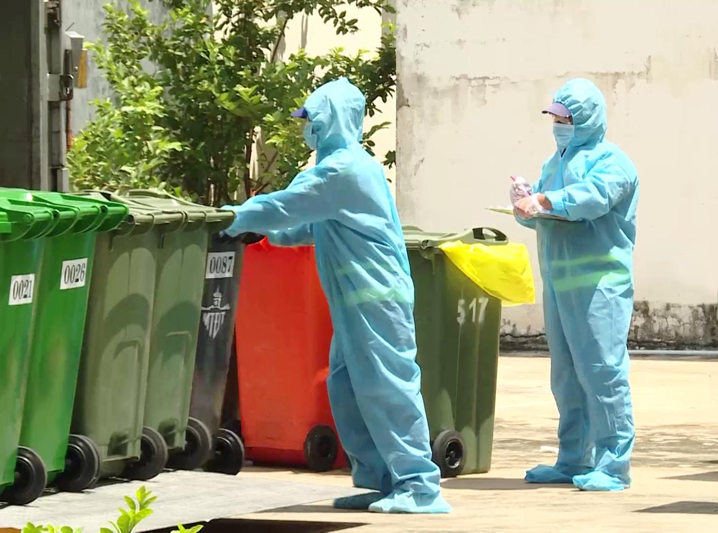 Công nhân Công ty TNHH một thành viên Môi trường đô thị TP.HCM thu gom chất thải tại một khu cách ly - ẢNH: SƠN VINH