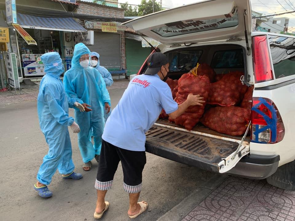 Anh chở rau củ đến nơi cần và hỗ trợ mang xuống xe để phân phát cho người dân.