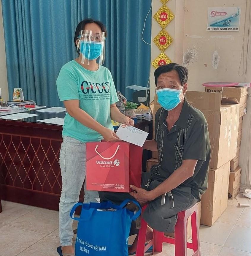 Cán bộ MTTQ Việt Nam quận 8 trao quà cho thương binh có hoàn cảnh khó khăn.