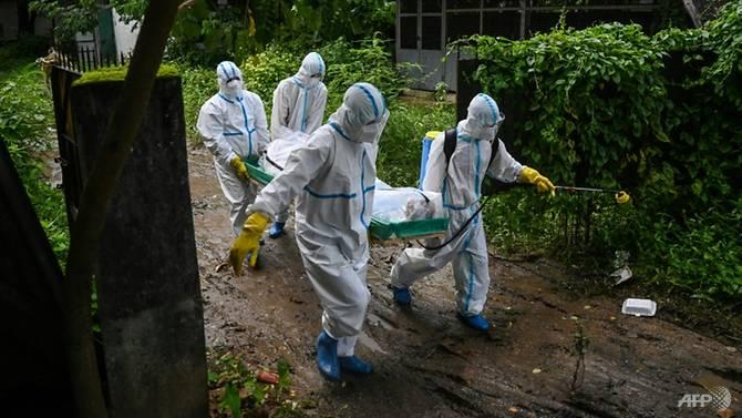 Các tình nguyện viên khiêng xác một nạn nhân COVID-19 đến nghĩa trang ở Yangon.
