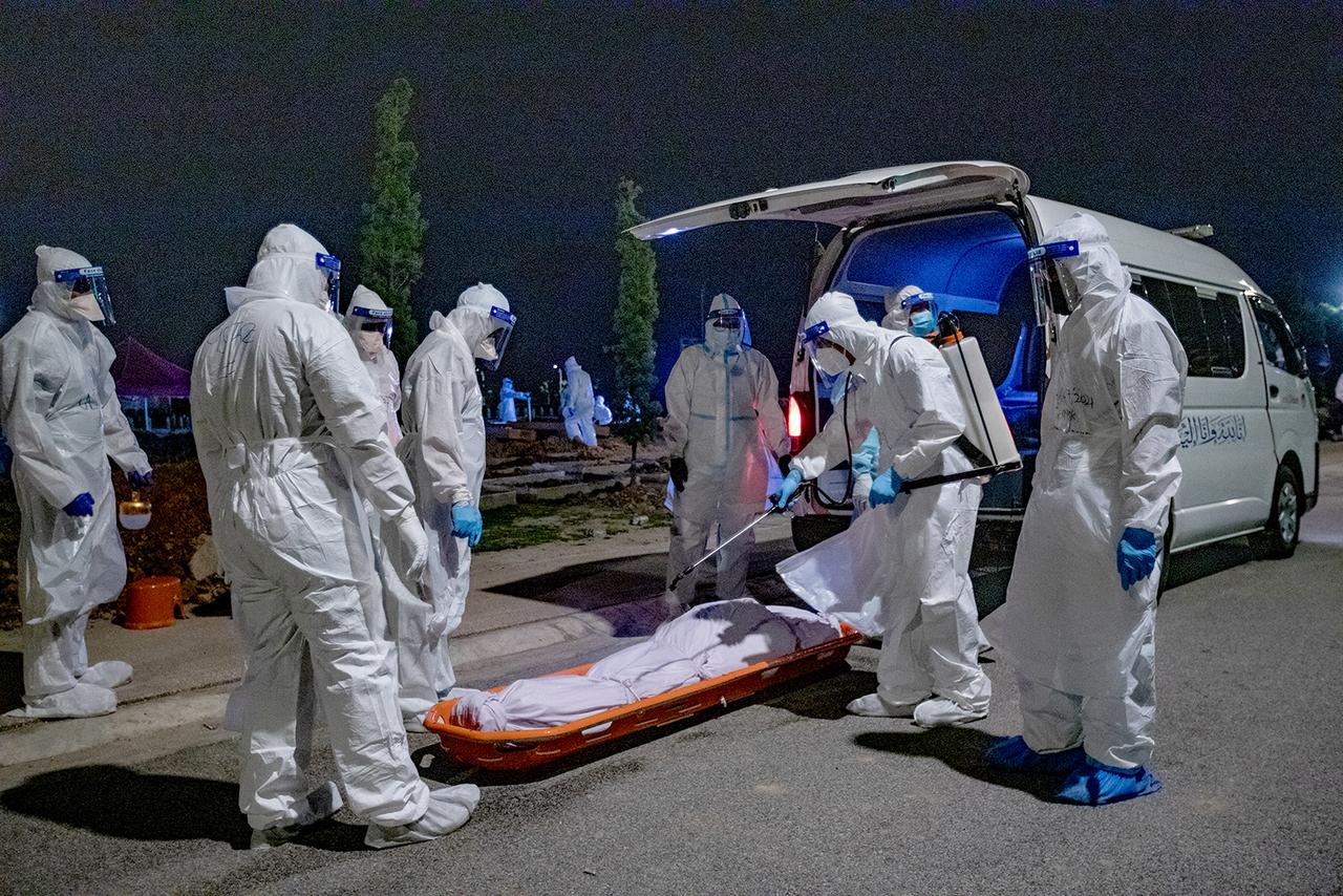 Thi thể của một nạn nhân Covid-19 được phun chất khử trùng trước khi chôn cất