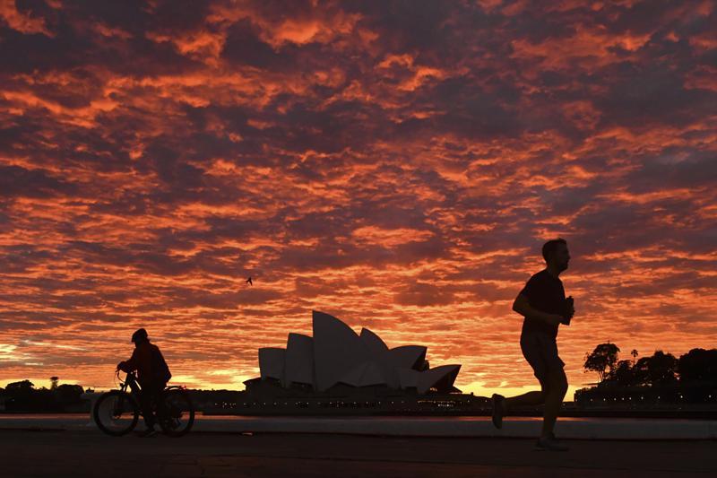 Một người chạy bộ chạy ngang qua Nhà hát Opera Sydney vào lúc bình minh ngày 28/7