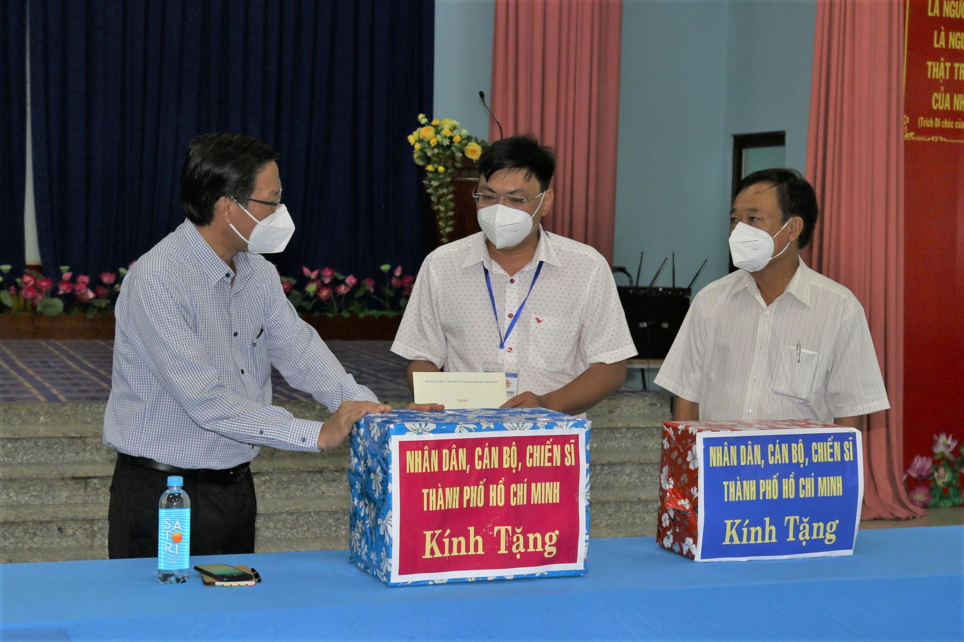 Phó bí thư Thường trực Thành ủy Phan Văn Mãi trao tặng UBND phường 7, quận 8 bốn phần quà bao gồm nước rửa tay, khẩu trang, kính chống giọt bắn...