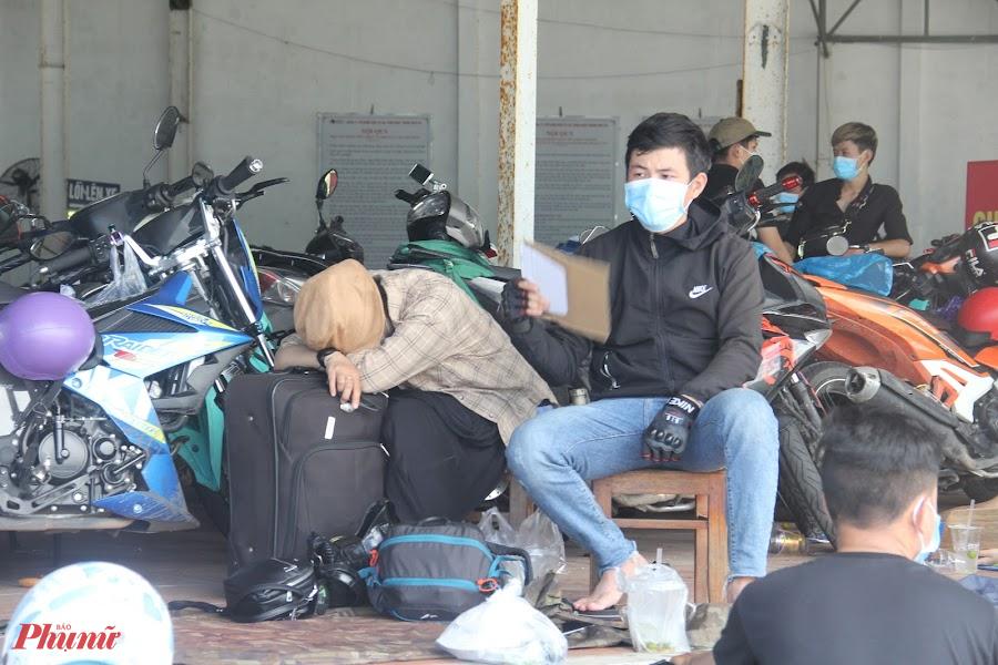 Nhiều ngừoi mệt mỏi ngồi đợi  làm thủ tục đưa đi cách ly tại Chốt kiểm soát số 5