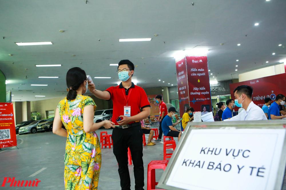 Người dân đi hiến máu được nhân viên y tế đo thân nhiệt từ bên ngoài, kiểm tra việc đeo khẩu trang và yêu cầu sát khuẩn, khai báo y tế.