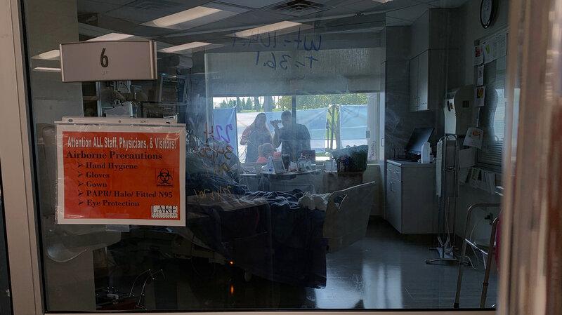 Các thành viên gia đình tập trung bên ngoài cửa sổ phòng bệnh của một bệnh nhân COVID-19 tại Bệnh viện Khu vực Lake ở Osage Beach, Missouri - Ảnh: AP