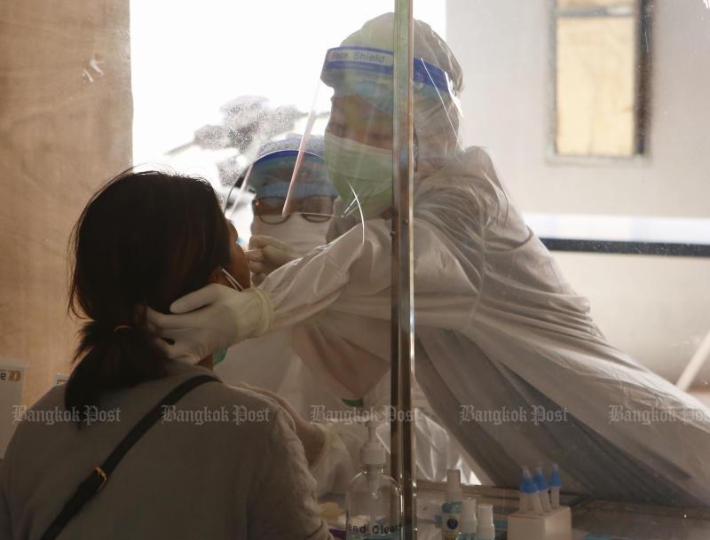 Các nhân viên y tế tiến hành xét nghiệm kháng nguyên nhanh cho một phụ nữ tại văn phòng tổ chức hành chính tỉnh ở huyện Muang, Pathum Thani, vào thứ Sáu. (Ảnh: Apichit Jinakul)