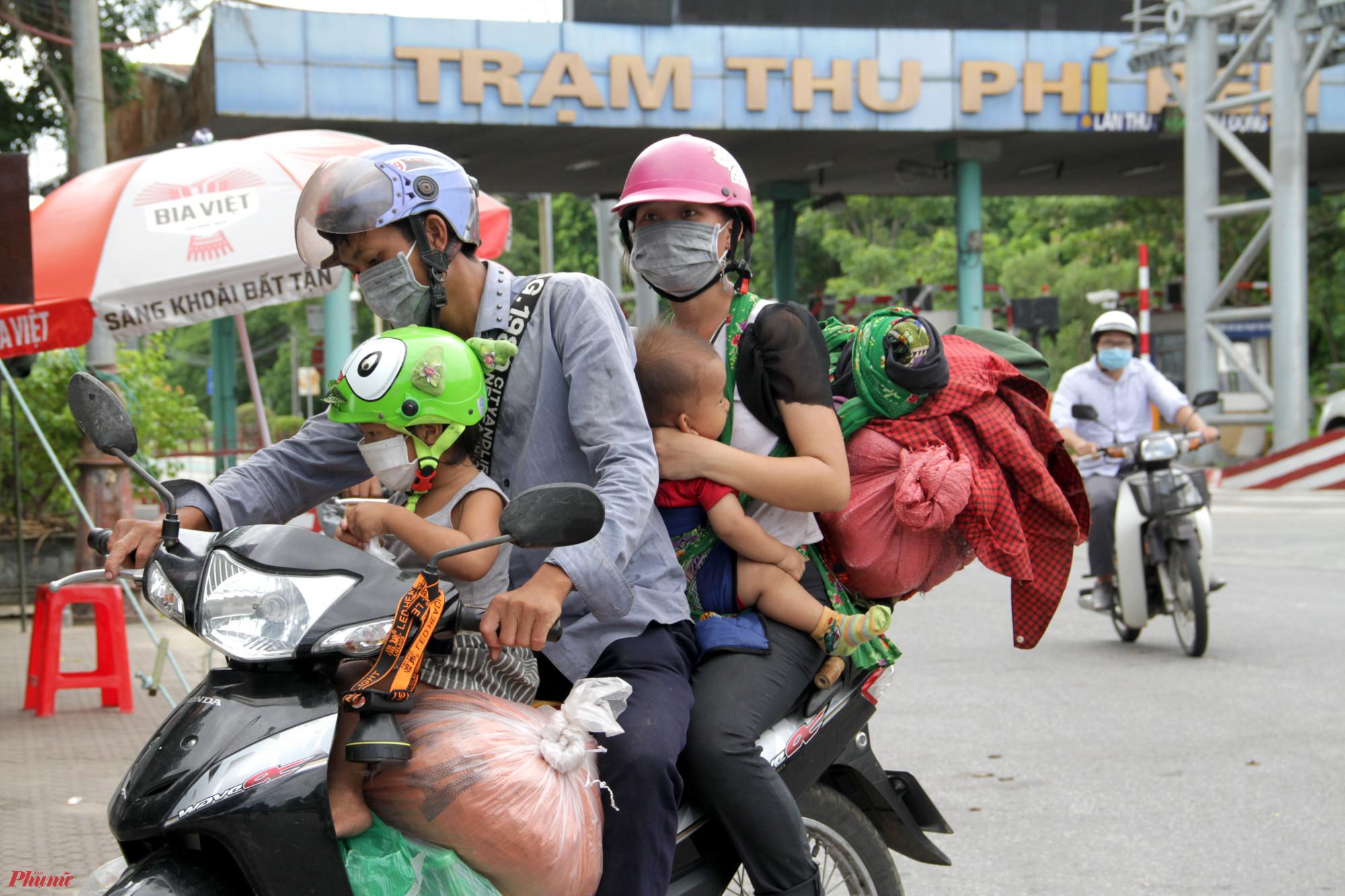 Nhiều gia đình ở Nghệ An chở theo con nhỏ chạy xe máy từ miền Nam về quê