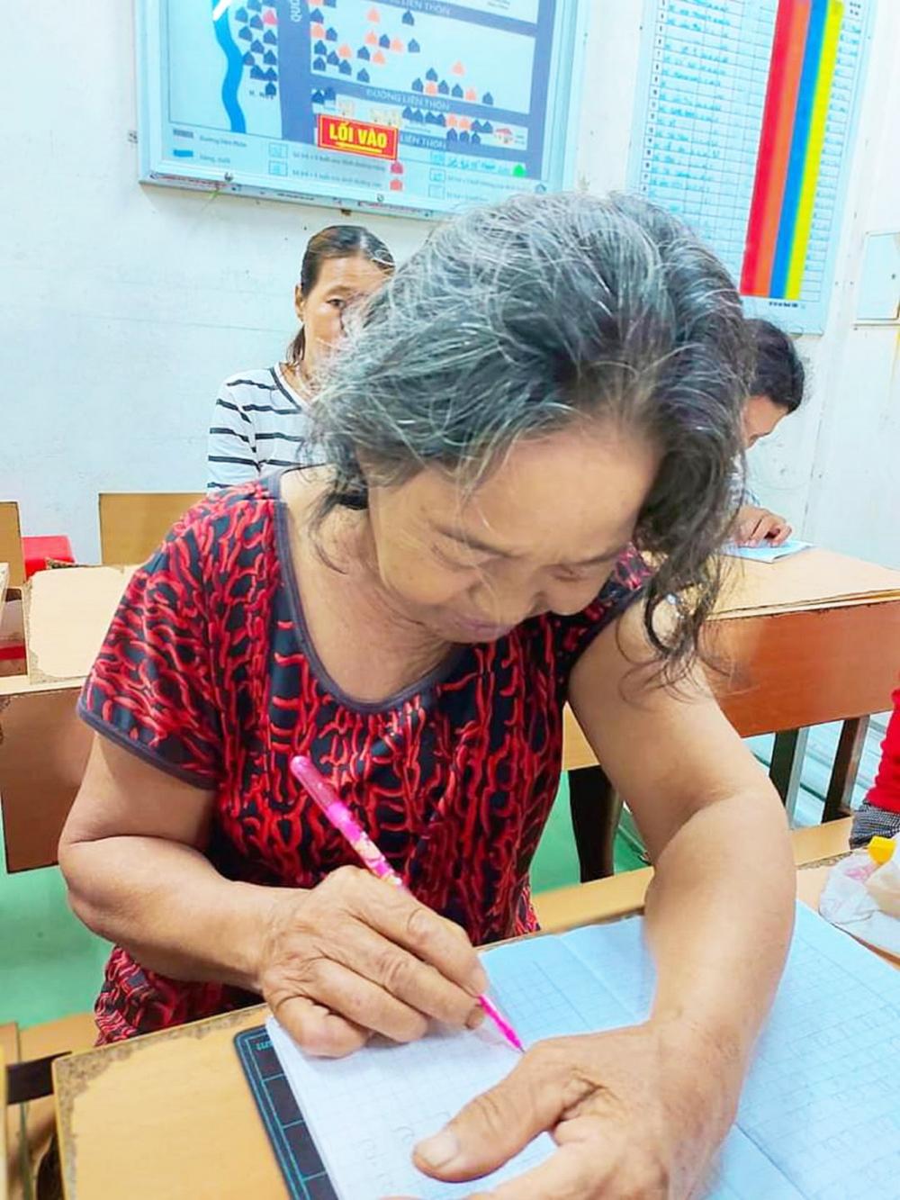 Gần 60 tuổi, bà Hồ Thị Dần đang nắn nót từng nét chữ để tự ký tên mình