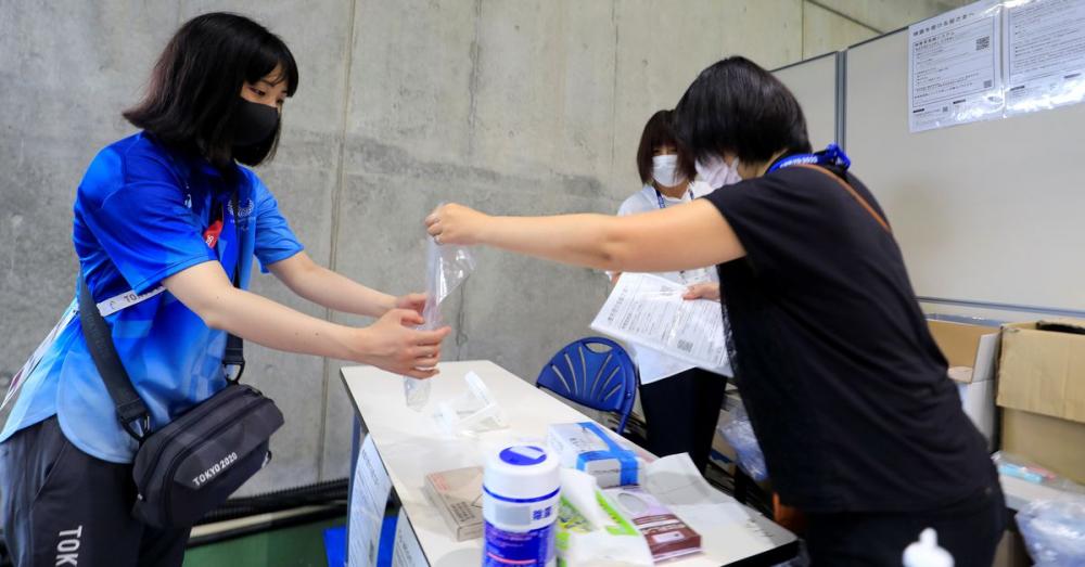 Một tình nguyện viên Thế vận hội 2020 đăng ký mẫu để xét nghiệm COVID-19 tại sân vận động Miyagi - Ảnh: Reuters