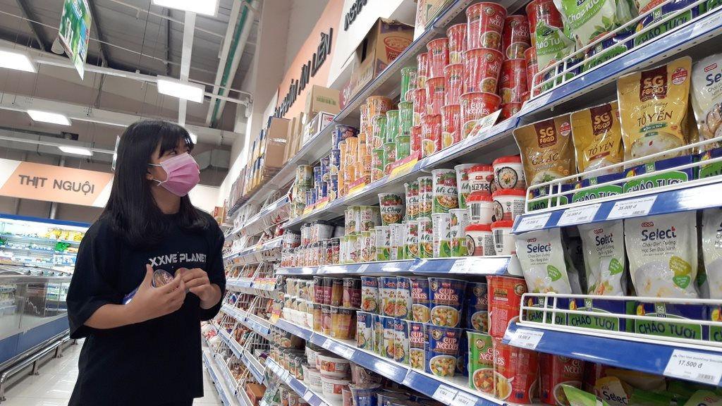 """việc đòi hỏi một hướng dẫn vừa nhất quán, vừa chi ly để trả lời """"hàng hóa, dịch vụ thiết yếu là gì"""" sẽ ít khả thi. Trong ảnh: Khách hàng đang chọn mua hàng hóa trong siêu thị"""