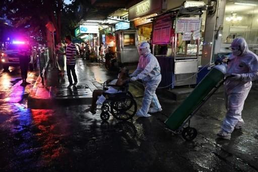 Một bệnh nhân Covid-19 lớn tuổi được các bác sĩ ở Bangkok đưa khỏi nhà để đến bệnh viện điều trị