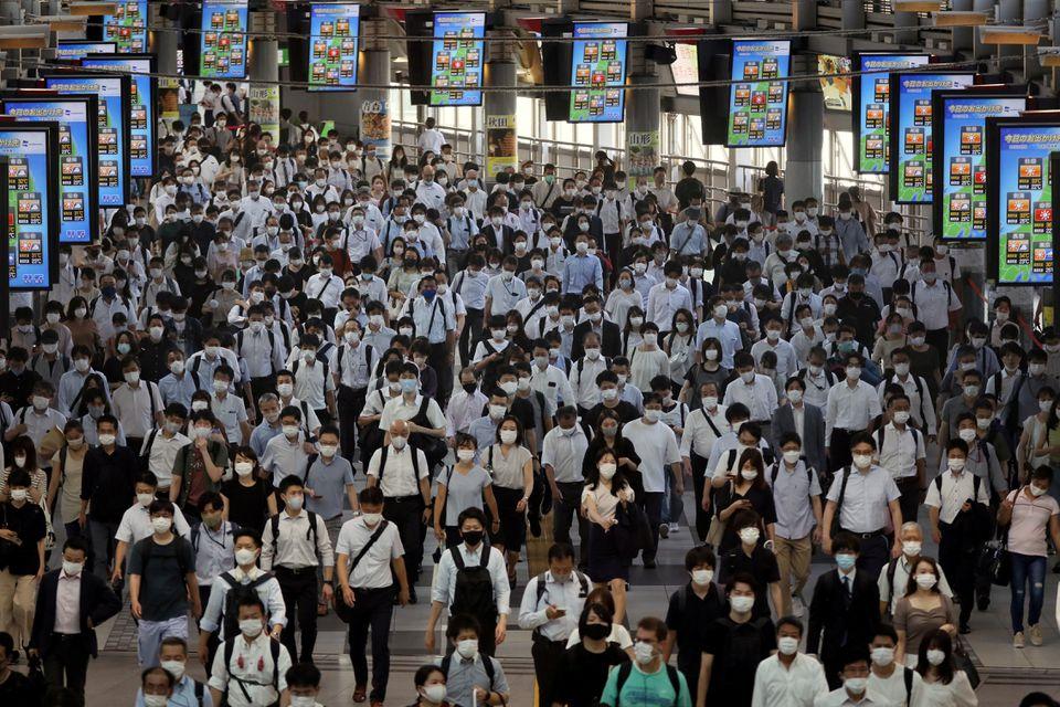 Những người đi làm đang đến ga Shinagawa vào đầu ngày làm việc, mọi người đều đeo khẩu trang khi dịch bệnh bùng phát trở lại ở Nhật Bản - Ảnh: Reuters